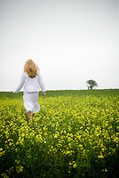 Blonde woman in white dress standing in field with yellow flowers