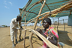 Aluel Yuot ties sticks together as she constructs a shelter in the internally displaced persons camp in Turalei, South Sudan. Families started arriving here shortly after fighting broke out in December 2013, and new families continued to arrive in March 2014 as fighting continued. Many are living in the open and under trees. The ACT Alliance is providing the displaced families and the host communities affected by their presence with a variety of support, including new wells. In the back is her husband, James Biar.
