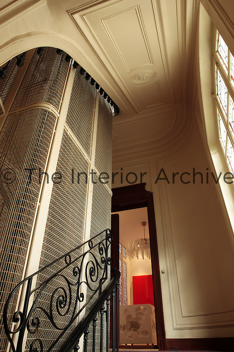 The communal area of the apartment block has a wrought iron staircase and an antique elevator