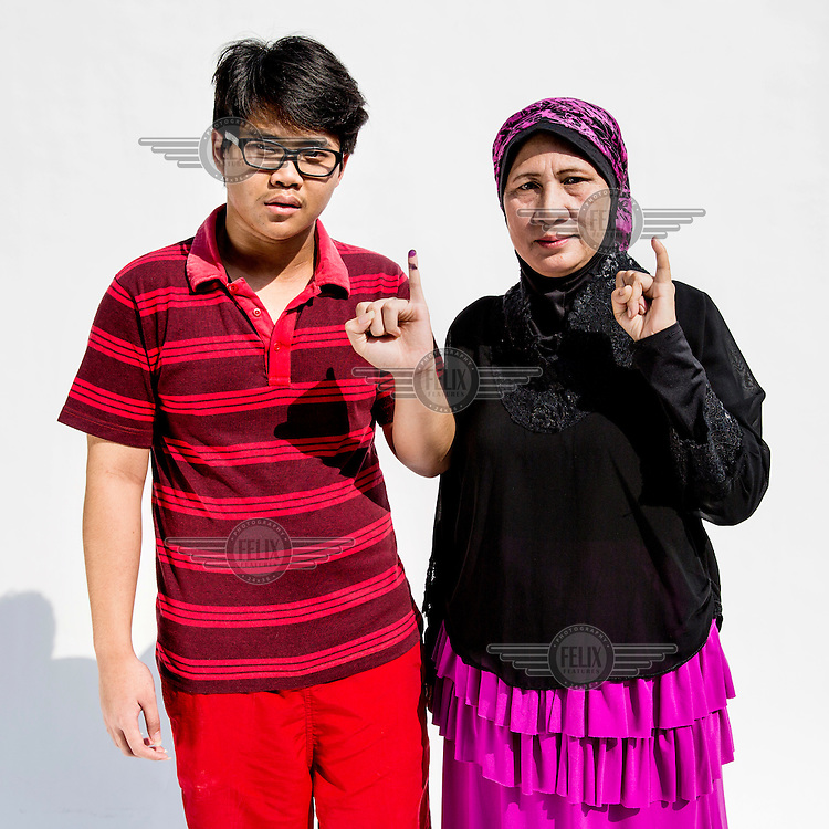 A mother and son flash a single finger sign, symbolising Indonesian presidential candidate Prabowo Subianto's candidacy number after they cast their votes at a polling station in Jakarta.