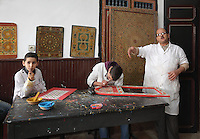 A lesson in painted woodwork at the Artisan School or Dar Sanaa, founded 1919 under the Spanish Protectorate of Morocco, which teaches the traditional art and craft skills of woodwork, zellige, sculpted plaster, leatherwork, etc, in Tetouan on the slopes of Jbel Dersa in the Rif Mountains of Northern Morocco. Tetouan was of particular importance in the Islamic period from the 8th century, when it served as the main point of contact between Morocco and Andalusia. After the Reconquest, the town was rebuilt by Andalusian refugees who had been expelled by the Spanish. Picture by Manuel Cohen