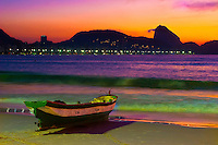 Sunrise at Copacabana beach with Sugar Loaf and fishing boat seen from south end by Posto Seis, Rio de Janeiro, Brazil.