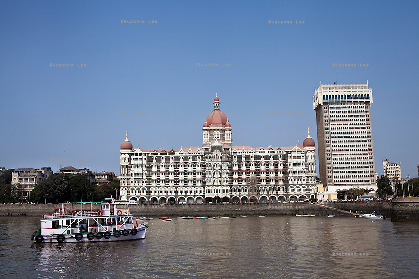 Tourist ferries pass in front of the Taj hotel that faces the Arabian sea on the Marine Drive in Mumbai, India. Photo by Suzanne Lee