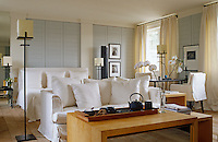In a spacious grey and white bedroom loose covers in crisp white linen on the sofa and armchairs match the bedlinen and covers on the double bed
