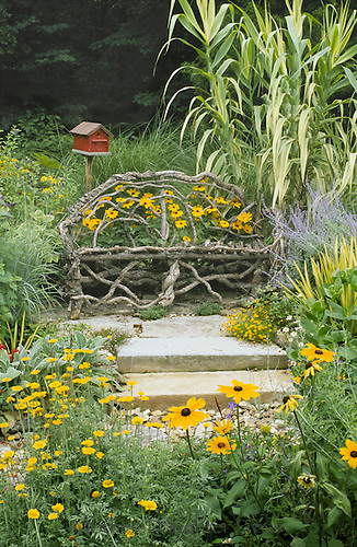 Handmade loveseat for the garden made of bent willow branches  becomes a focal point for a sunny garden spot full of blooming native flowers. Whimsical accents and art such as the birdhouse made to look like a red barn, add fun and can change.