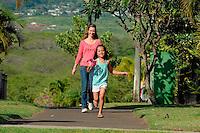 Mother and daughter walking in green lush neighborhood