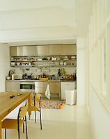 Stainless steel fronted kitchen units and appliances occupy one wall of this open-plan kitchen-dining area in a converted factory