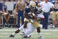 Annapolis, MD - September 9, 2016: Navy Midshipmen running back Calvin Cass Jr. (20) gets tackled by a Connecticut Huskies defender during game between UConn and Navy at  Navy-Marine Corps Memorial Stadium in Annapolis, MD. September 9, 2016.  (Photo by Elliott Brown/Media Images International)