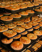 Meat pies on cooking trays.<br />