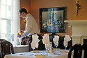 Waiter setting table in dining room at McCully House Inn, Jacksonville, Oregon.