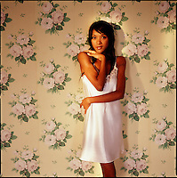 African American woman wearing white negligee leaning against floral wallpaper