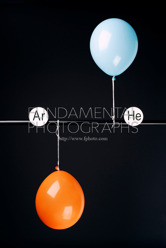 HELIUM AND ARGON FILLED BALLOONS<br /> (Variations Available)<br /> The Two Balloons Are Filled To The Same Volume<br /> Argon (orange balloon) is slightly denser than oxygen and does not rise. Helium (blue balloon) is less dense than oxygen and therefore rises.