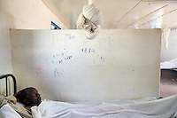 Somaliland. Waqohi Galbed province. Hargeisa. Tubeculosis (TB) hospital. Male ward. A black muslim man, TB patient, lays in his bed while he is taking the two months drugs as a TB treatment. Rolled mosqito net and white bed sheets. The Global Fund through the ngo ( Non-governmental organization ) World Vision supports the programm with a Tuberculosis grant (financial aid). Somaliland is an unrecognized de facto sovereign state located in the Horn of Africa. Hargeisa is the capital of Somaliland. © 2006 Didier Ruef
