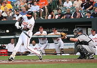 Adam Moore #10 of the Seattle Mariners watches Felix Pie #18 of the Baltimore Orioles make contact during a MLB game at Camden Yards, on August 8 2010, in Baltimore, Maryland. Orioles won 5-4 in extra innings.