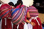 San Juan del Oro, Peru. Three women with manta bundles from the back.