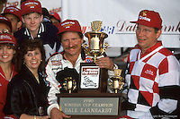 HAMPTON, GA - NOVEMBER 18: Dale Earnhardt celebrates in victory lane after clinching the NASCAR Winston Cup championship on November 18, 1990, at Atlanta Motor Speedway near Hampton, Georgia. The young boy in the upper left is Dale Earnhardt, Jr.