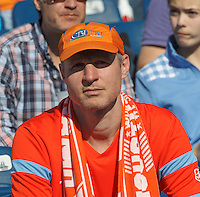 Houston Dynamo fan. In a Major League Soccer (MLS) match, the New England Revolution (blue/white) defeated Houston Dynamo (orange), 2-0, at Gillette Stadium on April 12, 2014.