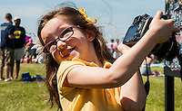 Sophia Rubin, 4, from Pronceton, NJ, takes a photo of the graffiti wall in the infield on Preakness Day at Pimlico Race Course on May 19, 2012