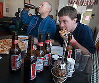 Mark Miser, left, downs a beer as his dining partner, Josh Groves, bites into a pizza at Michael's Pizza  Friday, January 13, 2006, on the first day of alcohol sales in downtown Westerville, Ohio. A ballot issue in the November 2005 election approved alcohol sales in downtown Westerville, home to the Anti-Saloon League. Michael's Pizza is one of several new alcohol sales permits in the city. Alcohol was last served in the city more than 120 years ago.<br />