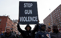 A man holds a poster as he takes part during a rally against gun violence in Harlem March 21, 2013 in New York City . VIEWpress/ Kena Betancur.