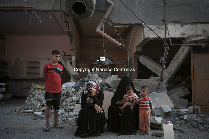 """In this Saturday, Aug. 16, 2014 photo, a Palestinian family sit at the entrance of their house after it was partially distroyed by artillery shelling during the """"Protective Edge"""" Israeli military operation in Beit Hoanoun neighborhood in Gaza City. After a five days truce was declared on 13th August between Hamas and Israel, civilian population went back to what remains from their houses and goods in Gaza Strip. (Photo/Narciso Contreras)"""