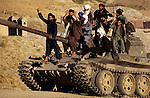 Unidentified Taliban soldiers ride on tank on July 25, 1996 outside Kabul, Afghanistan. Taliban took over most of the country in 1996, and imposed strict Muslim Sharia law. Women were not allowed to work or go to school. Taliban was ousted from power in the fall of 2001. (Photo by: Per-Anders Pettersson).