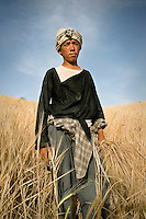 A farmer standing in a field of wheat.