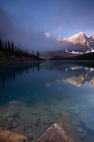 Reflection of the Ten Peaks in Turquoise Waters of beautiful Moraine Lake in the early morning as fog rolls into the valley