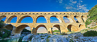 Picture of the ancient Roman Aqueduct of the Pont du Gard which crosses the River Gardon near Vers-Pon-du-Gard, France. Part of the 50 km long aqueduct that served the Roman town of Nemausus (Nimes) its 3 tiers of arches stand 48 m high (160 ft). A UNESCO World Heritage Site.