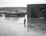 A breeches buoy, a device for rescuing people at sea, saved three employees of the Casertano Produce Co. at 76 Freight Street., during the height of the flood. Halfway across is George Nobile. An unidentified Guardsman supervises the operation.