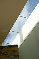 A summer shower of rain on the flat glass roof of a corridor creates intricate shadows