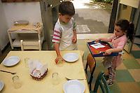"""Nel quartiere di San Lorenzo, a Roma il 6 gennaio 1907, Maria Montessori inaugura la prima """"Casa del bambino"""" . """"Aiutami a fare da solo"""" è lo slogan del metodo montessoriano..In the district of San Lorenzo in Rome in January 6th, 1907, Maria Montessori inaugurated the first """"Children's House"""". """"Help me to do alone"""" is the slogan of the Montessori method..Bambini nella scuola mentre giocano e imparano. Children  learn while playing in school...."""