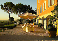 The Hotel Villa Fontalunga in Italy where a grove of umbrella pines and neatly clipped shrubs create a  Mediterranean feel to the elegant gravelled terrace