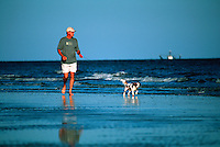 Man walking his dog along the water edge at the beach.