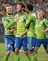 From left, Seattle Sounders FC forward Roger Levesque, forward Brad Evans and defender James Riley celebrate after Evans scored on a penalty shot during play against Toronto FC at Qwest Field in Seattle Saturday April 30, 2011. The Sounders won the game 3-0.
