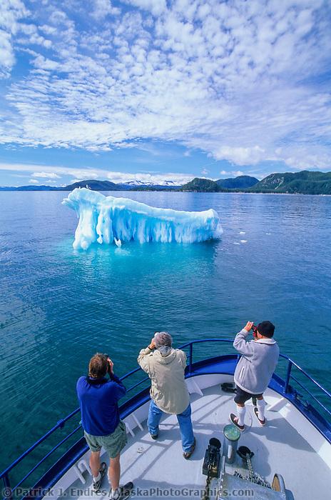 Tourist and floating glacier iceberg, altocumulous clouds, Prince William Sound, Alaska