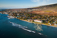 Sunset creates an intense reflection of a hotel onto the relatively calm ocean, with surfers and boat harbor to the left, Maui.