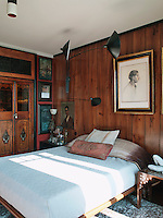 In contrast to the guest bedroom, the master bedroom has a chic understated charm to it, clad in simple wood panelling with natural tones