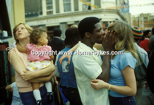 Notting Hill carnival 1970s west London Black male white female young adult couple kissing. mixed race child.