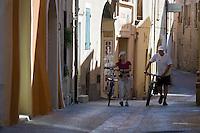 Europe/France/Languedoc-Roussillon/30/Gard / Saint-Quentin-la-Poterie: touristes à bicyclette dans les ruelles du village