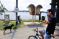 """Singapore. Pulau Ubin island. South china sea. A father and his son use a tandem bike on a sunny saturday. The man talks on his mobile phone. A sign says """" Please do not litter"""". A childs calls from a public phone box. © 2001 Didier Ruef"""