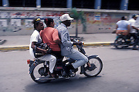 Three people riding a small motorcycle in the city of Barahona, Dominican Republic