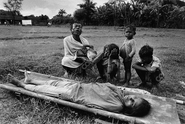 Grieving husband and family with the body of their mother who died from cholera, border of India and Bangladesh, 1971.