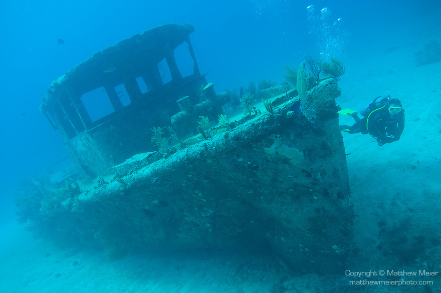 Grand Bahama Island, The Bahamas; a scuba diver swims past the bow of the 'Badger' wreck, this tugboat was intentionally sank near the site of Papa Doc's Wreck, sitting upright on the sandy bottom in 50 feet of water, it now serves as an anchor for the mooring line, the Papa Doc wreck sank during a violent storm and rough seas in 1968, while transporting mercenaries and firearms to Haiti during their uprising over dictator Papa Doc Duvalier, the wreck has been broken up and scattered and the only visible remains of the original ship are it's engine blocks