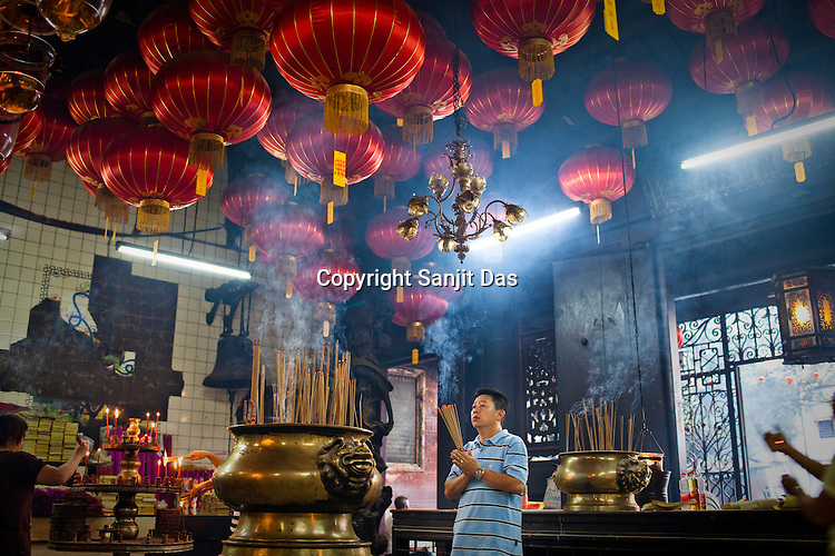 A devout Chinese devotee prays at the Goddess of Mercy temple in the UNESCO heritage city of Georgetown in Penang, Malaysia. Photo: Sanjit Das/Panos