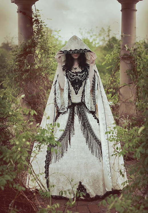 A young woman wearing a long Victorian dress outdoors with hood covering face