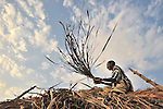 John Lago puts a thatched roof on his hut in Pisak, a small village in Central Equatoria State in Southern Sudan. NOTE: In July 2011, Southern Sudan became the independent country of South Sudan