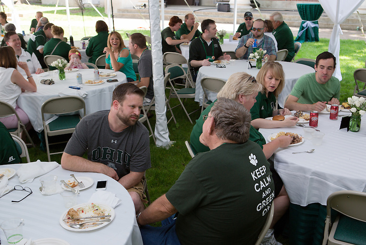 """Elliot Strunk, center, and another member of the Ohio University alumni community chat  at a barbecue on the College Green on May 31, 2014. The event, for Ohio University alumni and their families, was part of the """"On The Green"""" weekend, which was hosted by the Ohio University Alumni Association. Photo by Lauren Pond"""