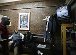 Men watch television at a barber shop in Harlem New York NY .Tuesday Nov 4 2008.  Millions of voters across the United States went to the polls in record numbers to choose between Presidential candidates Barack Obama and John McCain.. Photo by Eyal Warshavsky .