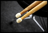 Tips of a pair of drumsticks on drummer's throne